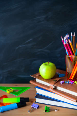 Back to School cocept. Still life with school books, pencils and apple against blackboard background. Close up Banco de Imagens