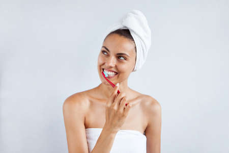 Smiling happy young woman with healthy teeth holding a tooth brush white background. Clean beauty and healthy concept 写真素材