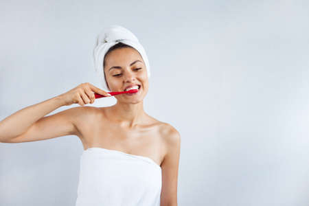Smiling happy young woman with healthy teeth holding a tooth brush white background. Clean beauty and healthy concept Stockfoto