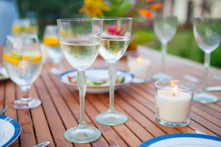Two glasses of white wine. Family outdoor dinner in the garden in summertime at sunset. Picnic food and drink concept