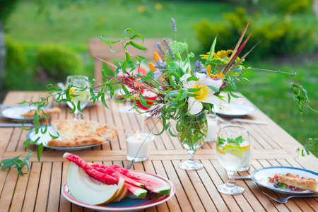 Family outdoor dinner in the garden in summertime at sunset. Picnic food and drink concept