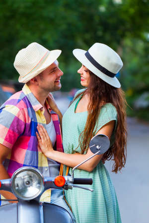 Young happy couple in love riding a vintage scooter in the street wearing hats. Holiday and travel concept 스톡 콘텐츠