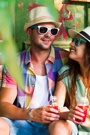 Happy smiling couple in sunglass and hat  with guitar drinking juice spending carefree time together. Travel and love concept