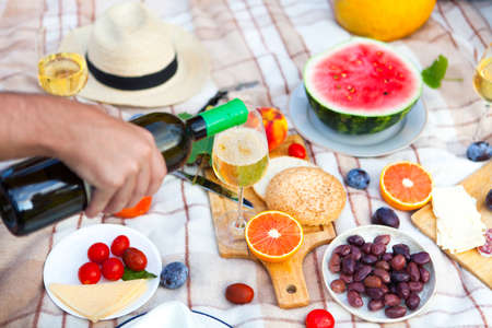 Summer Picnic Basket on the Green Grass in italian garden. Food and drink concept. Friends Party time