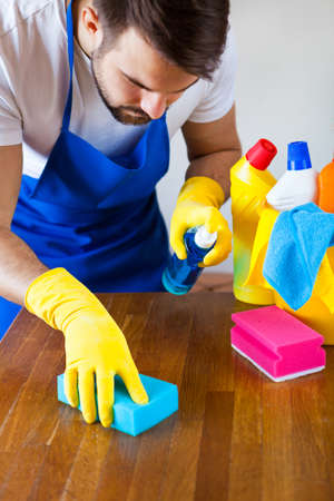 Closeup Of Young Man Wearing Apron Cleaning Kitchen Worktop, set cleaning concept 스톡 콘텐츠