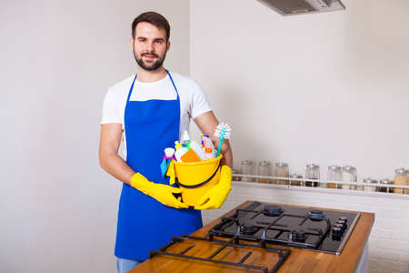 Man holding plastic bucket with bottles and brushes, gloves and detergents in the kitchen, on white background, set cleaning concept. 스톡 콘텐츠