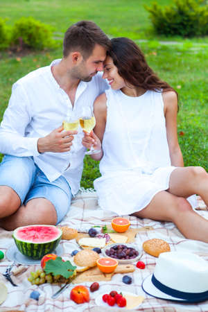 Yong couple on Summer Picnic Basket on the Green Grass in italian garden. Food and drink concept. Family Party time