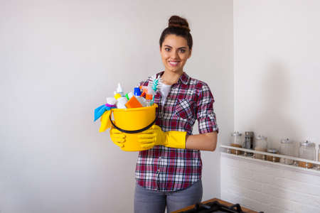 Young pretty woman holding cleaning tools and products in bucket, on white citchen,  cleaning concept, set.