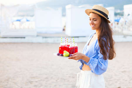 Happy woman holds a dish with a drinks red juice at sunset. Picnic theme on the beach, food and drink concept 스톡 콘텐츠