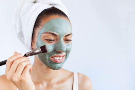 Young beautiful woman in face mask of therapeutic blue mud.