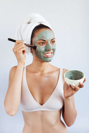 Young beautiful woman in face mask of therapeutic blue mud. Spa treatment, self care and healthy skin. Copy space, white background