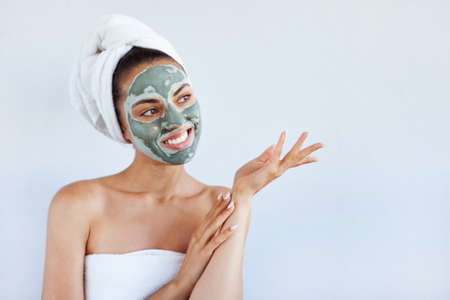 Young beautiful woman in the face mask of therapeutic blue mud.