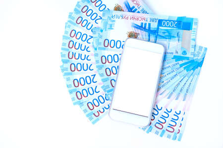 Background of money Russian banknotes currency roubleand and cell phone. in nominal value of two thousand. New tickets bank Russia. Close up. Rich concept