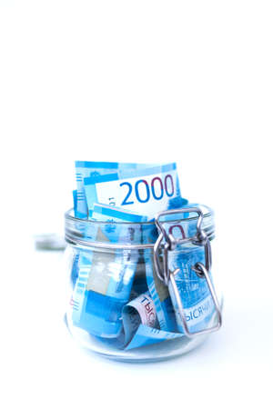 Paper Russian Money. New Russian Banknotes Of 2000 Two Thousands Rubles Close Up in glass jar on white isolated background. Saving money concept. Stockfoto - 109550557