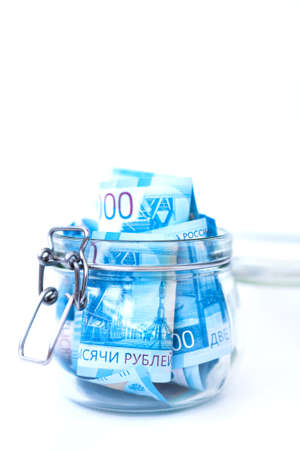 Paper Russian Money. New Russian Banknotes Of 2000 Two Thousands Rubles Close Up in glass jar on white isolated background. Saving money concept. Stockfoto - 109550562