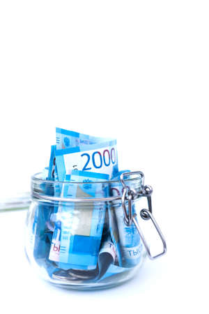 Paper Russian Money. New Russian Banknotes Of 2000 Two Thousands Rubles Close Up in glass jar on white isolated background. Saving money concept.
