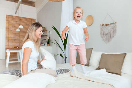 Mother and her daughter child girl playing and hugging in bedroom. Happy loving family.