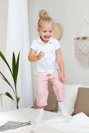 Portrait Little pretty smiling girl playing and jumping in bedroom Stockfoto