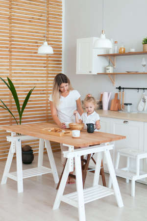 Happy family mom and daughter prepare dough for baking sitting at table in kitchen looking at each other