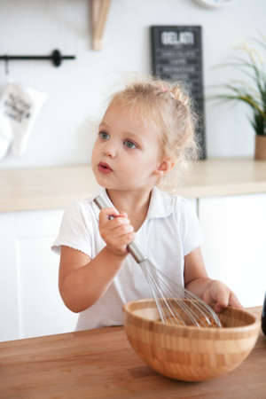 Children girl Cooking in kitchen. Happiness Kid Home Concept