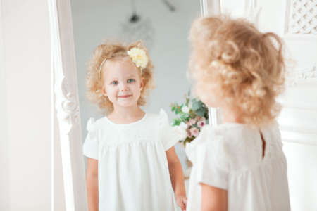 Little pretty girl in white dress playing in home Stockfoto