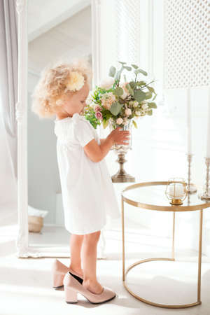 Little pretty girl in white dress trying on mummys shoes, indoor