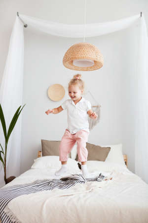Portrait Little pretty smiling girl playing and jumping in bedroom Reklamní fotografie