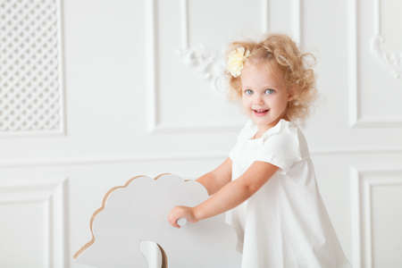 Little pretty girl in white dress playing indoor