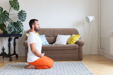 Man practicing yoga and meditation at home. A series of yoga poses. Lifestyle concept. Reklamní fotografie - 127536342