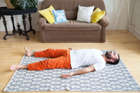 Man practicing yoga and meditation at home. A series of yoga poses. Lifestyle concept. Reklamní fotografie - 127536347