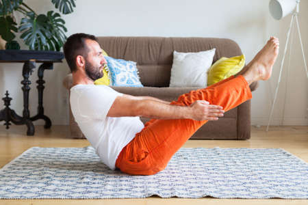 Man practicing yoga and meditation at home. A series of yoga poses. Lifestyle concept. Stockfoto