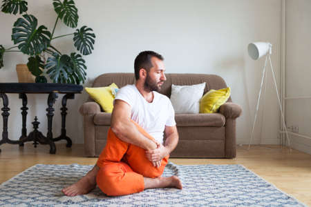 Man practicing yoga and meditation at home. A series of yoga poses. Lifestyle concept. Archivio Fotografico