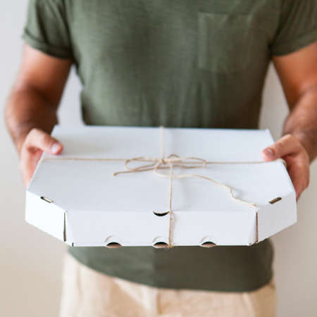 Food delivery service. A man holding in hands a box of pizza on a white background. Close up Archivio Fotografico