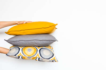 Colorful pillows in womens hands on a white isolated background, the concept of home comfort