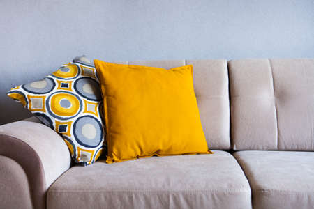Multi-colored pillows on a beige fabric sofa, the concept of home comfort and cozy, copy space, close-up Reklamní fotografie