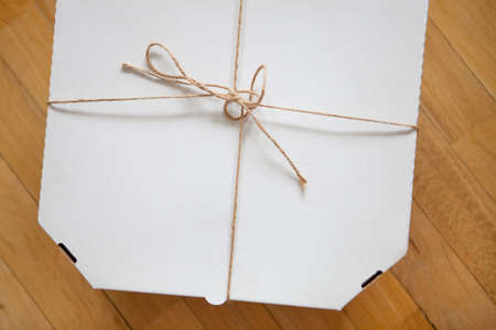 Close up of a white pizza box template on wood background. Archivio Fotografico
