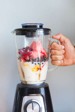 Mens hand hold blender filled with fresh whole fruits for making a smoothie or juice. Healthy eating concept. Close Up Reklamní fotografie