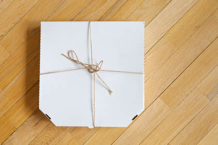 Close up of a white pizza box template on wood background. Reklamní fotografie