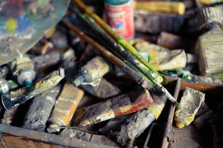 Oil paints and brushes on the old easel and color palette and tubes of the artist