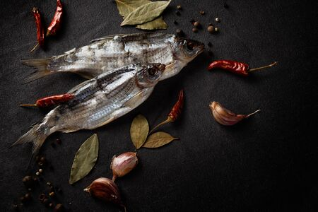 Still life of dried fish with spices on a black background with a beautiful light