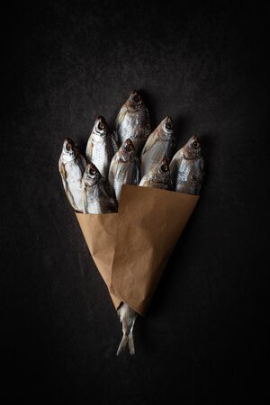 A bunch of dried fish on a black background with craft paper with a beautiful light