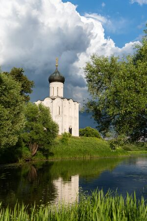 Orthodox church on a green meadow with trees and blue cloudy sky in beautiful evening light