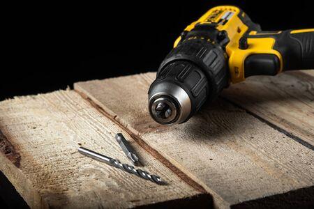 Elektrische gelbe Bohrmaschine Nahaufnahme auf schwarzem Hintergrund mit Holz und Bohrern. Elektrische Werkzeuge. Hand-Akku-Schraubendreher. Standard-Bild
