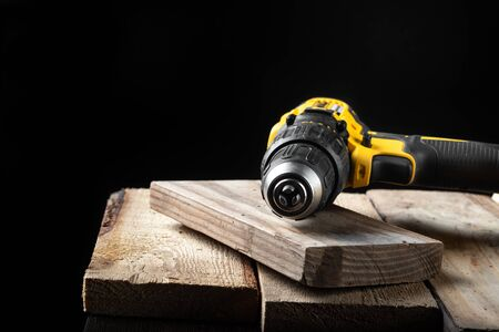 Electric yellow drill closeup on a black background with wood and drills. Electrical tools. Hand battery screwdriver. Stok Fotoğraf