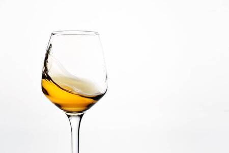 Beautiful glass with a splash of white wine on white background close-up
