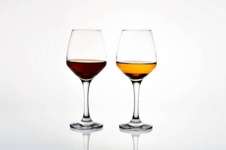 Two glasses of red and white wine on a white background. Side view. 免版税图像