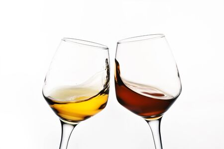 Beautiful glass with splash of red and white wine on a white background close-up. Side view.