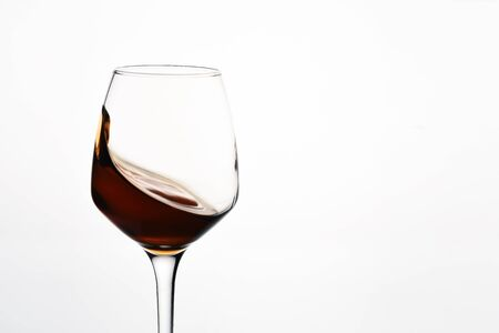 Beautiful glass with a splash of red wine on white background close-up 免版税图像