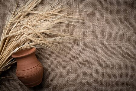 Yellow dry spikelets of wheat on a burlap with a clay pot. Place for text. Still life close up. 免版税图像