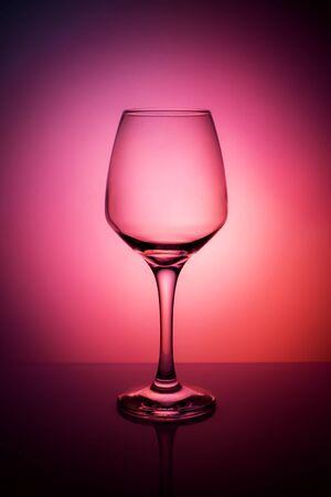 Wine glass on a purple red orange background. Still life with a beautiful light. 免版税图像